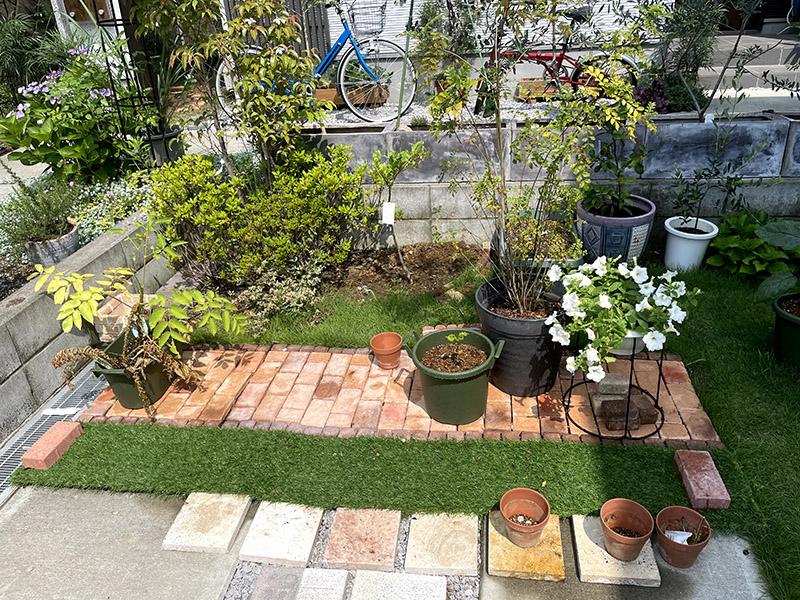 レンガタイルと人工芝のある庭